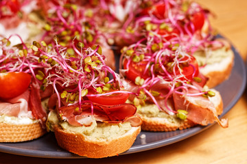 Small fresh homemade sandwiches with bread, avocado paste, sprouts, Parma ham and coctail tomato prepared to house party