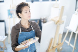 Young woman with palette concentrating on painting on easel in modern studio - 221703630