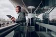 Leinwanddruck Bild - Found it amusing. Waist up portrait of businessperson near terminal looking at gadget and smiling