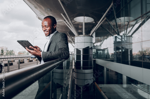 Leinwanddruck Bild Found it amusing. Waist up portrait of businessperson near terminal looking at gadget and smiling