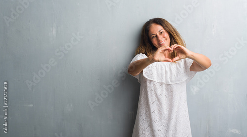 Leinwanddruck Bild Middle age hispanic woman standing over grey grunge wall smiling in love showing heart symbol and shape with hands. Romantic concept.