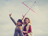 Two fashionable women and umbrella - 221725444