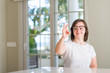 Down syndrome woman at home doing ok sign with fingers, excellent symbol