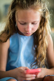 Little girl playing on mobile device - 221739239