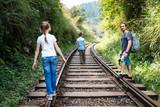 Family walking along train tracks - 221739447
