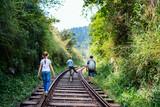 Family walking along train tracks - 221739494