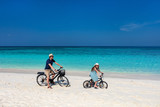Father and daughter riding bikes at tropical beach - 221739889
