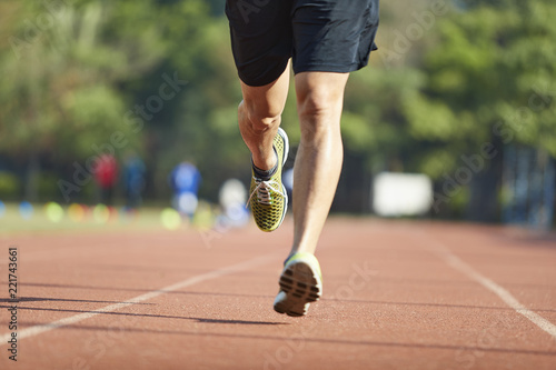Fototapeta young asian male athlete running on track