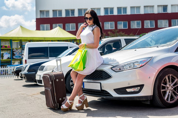 Beautiful brunette with suitcase and shopping bags