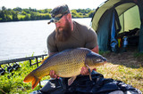 Happy angler with carp fishing trophy - 221745843