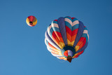 Two hot air balloons flying high in the blue sky - 221746407