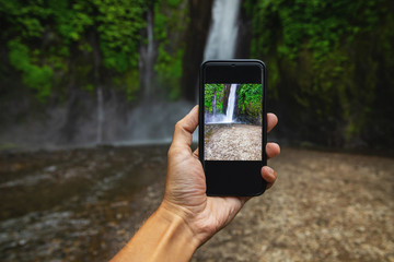 Man taking picture of a beautiful waterfall © blackday