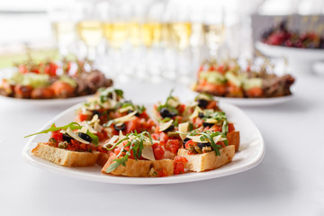 Plate with Italian appetizers. Bruschetta with a cherry tomatoes and shrimps. Parmesan cheese, olives, sun-dried tomatoes and walnuts.