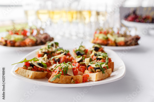 Plate with Italian appetizers. Bruschetta with a cherry tomatoes and shrimps. Parmesan cheese, olives, sun-dried tomatoes and walnuts. - 221748848