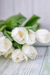 Beautiful white tulips on a light wooden background. Free space