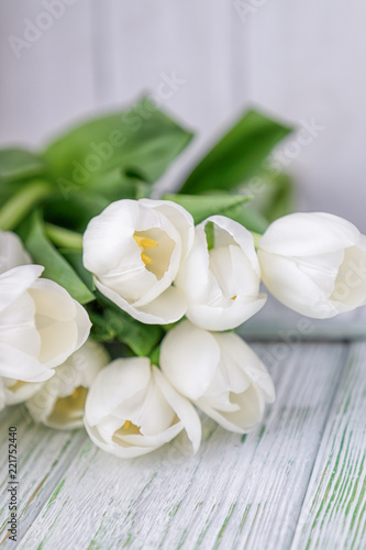 Fototapeta Beautiful white tulips on a light wooden background. Free space