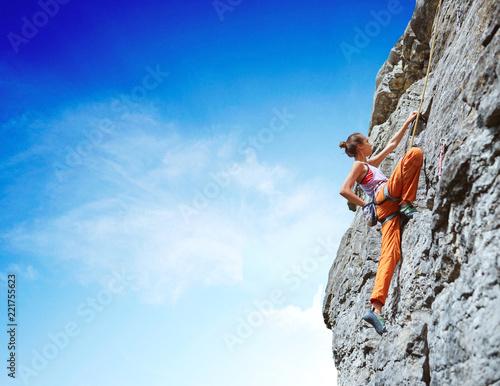 Leinwandbild Motiv young slim female rock climber climbing on the cliff