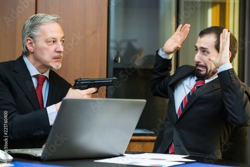 Leinwanddruck Bild Man threatening a colleague with his gun