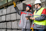 Waist up portrait of modern bearded worker  wearing warm jacket and hardhat pointing up while discussing production with foreman  in workshop, copy space - 221767263