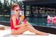 Digital generation. Happy joyful woman using her smartphone while sitting near the pool