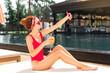 Beautiful photo. Happy joyful woman taking a selfie while sitting near the swimming pool