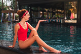 Near the pool. Nice attractive woman smiling while looking at her hand - 221772834