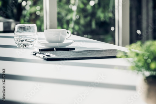 Leinwandbild Motiv Close up business contract paper on meeting room table with pen and coffee cup in sun light shadow with green plant at office,business agreement concept.