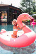 Joyful mood. Happy nice woman holding an air flamingo while having fun in the pool