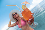 Woman drinking cocktail on the beach