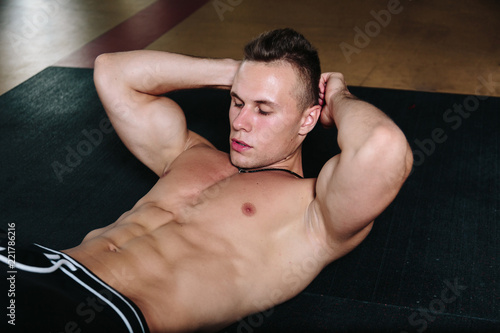 Leinwandbild Motiv Model sports young athletic man exercising in gym.Muscular man during workout in the gym.Portrait of sporty healthy strong muscle.Fitness trainer.Sport workout bodybuilding motivation concept