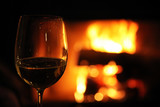 Glass with red wine on the background of fire in the fireplace, coziness and warmth at home - 221786684
