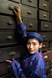 Asian pharmacist working at oriental pharmacy from the 19th century. Woman in traditional costume eastern druggist in the ancient drug store. - 221787624