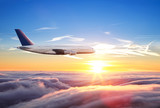 Huge two-storey passengers airplane flying above clouds - 221789271