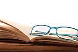 Reading glasses on wood table with open book front - 221798292