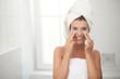 Junge hübsche Frau trägt Gesichtscreme auf