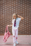 Cute schoolgirl playing with the bag in a street