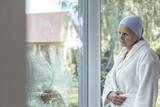 Lonely woman with cancer standing next to a window - 221825406