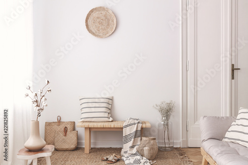 Flowers on wooden table near bench with pillow and blanket in white living room interior. Real photo
