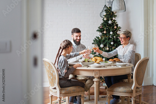 Fototapeta Family of three having lunch for Christmas holidays