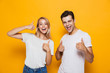 Young loving couple standing isolated over yellow wall background showing thumbs up gesture.
