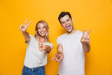 Excited young loving couple standing isolated over yellow wall background showing peace gesture. - 221827029