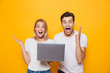 Happy excited young loving couple isolated over yellow wall background using laptop computer. - 221827281