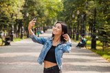 An Asian girl takes a picture of herself on the phone for a walk. - 221831044