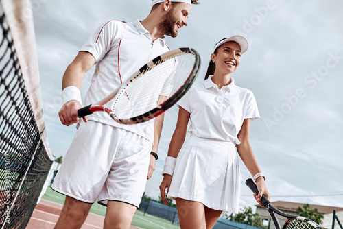 Fototapeta Enjoying spending time on the court. Beautiful young couple walking on the tennis court with smile.