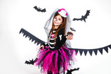 Happy girl in a skeleton costume having fun indoor - 221838048