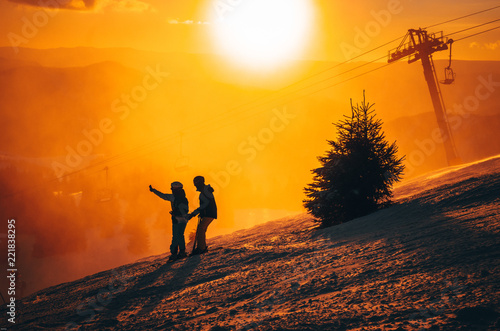 Silhouette of two skiers in winter nature. Ski resort, sunset light
