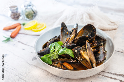 Mussel with white wine sauce on table - 221839806