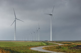 road between wind turbines on cloudy day - 221842220