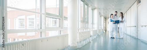 Leinwanddruck Bild Drei Ärzte im Flur von Krankenhaus unterhalten sich kurz