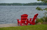 Two red Muskoka / Adirondack chairs at a lake - 221843428